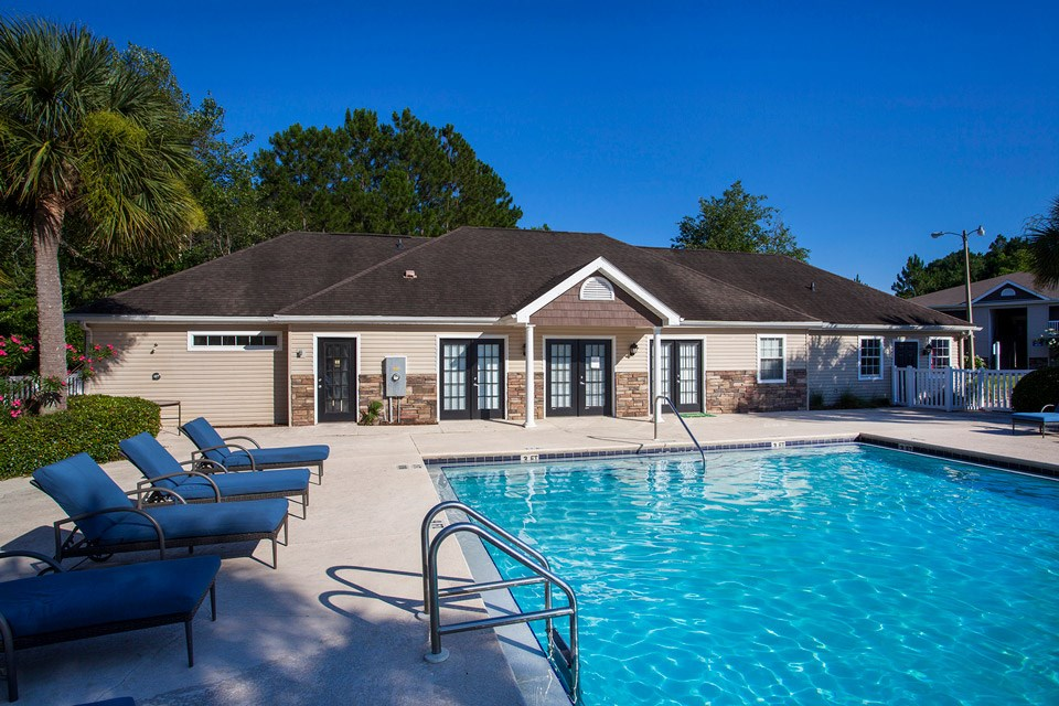 The crystal clear blue water of the swimming pool awaits resident swimmers at Crystal Lake Apartments in Pensacola, FL